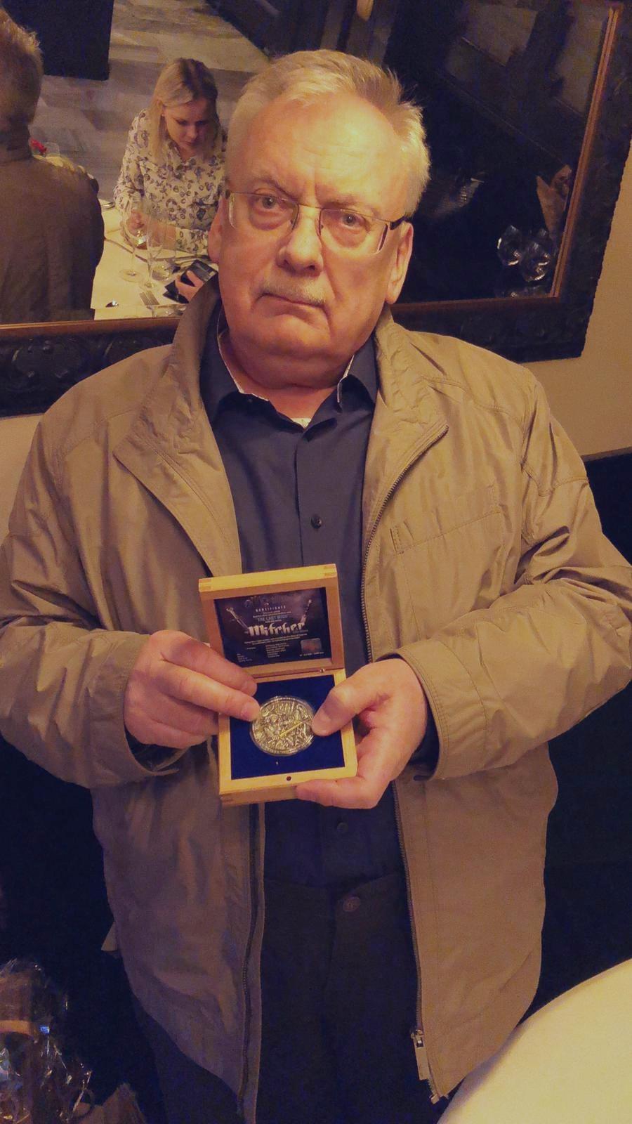 Andrzej Sapkowski prezentuje jedną z monet z serii Wiedźmin.