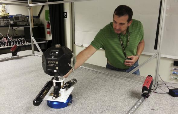 Smart SPHERES project manager Chris Provencher demonstrates one of NASA's robots at the Ames Research Center in Mountain View, California