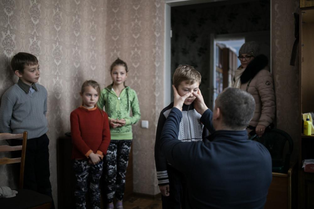 Zdjęcie pojedyncze - III miejsce w kategorii ŻYCIE CODZIENNE. Fot. Marta Rybicka, Naddniestrzańska Republika Mołdawska, Słoboda Raszkowska. Chłopiec z polskiej rodziny mieszkającej w tej republice właśnie miał wypadek. Z grupą dzieci jechał na zajęcia muzyczne, gdy nagle samochód wpadł w poślizg i zderzył się z drugim jadącym z naprzeciwka. Na szczęście dzieci doznały tylko drobnych obrażeń. Na zdjęciu polski ratownik medyczny, który przyjechał w ramach Charytatywnej Akcji Mikołajkowej, ogląda i pociesza chłopca. 15 grudnia 2018.
