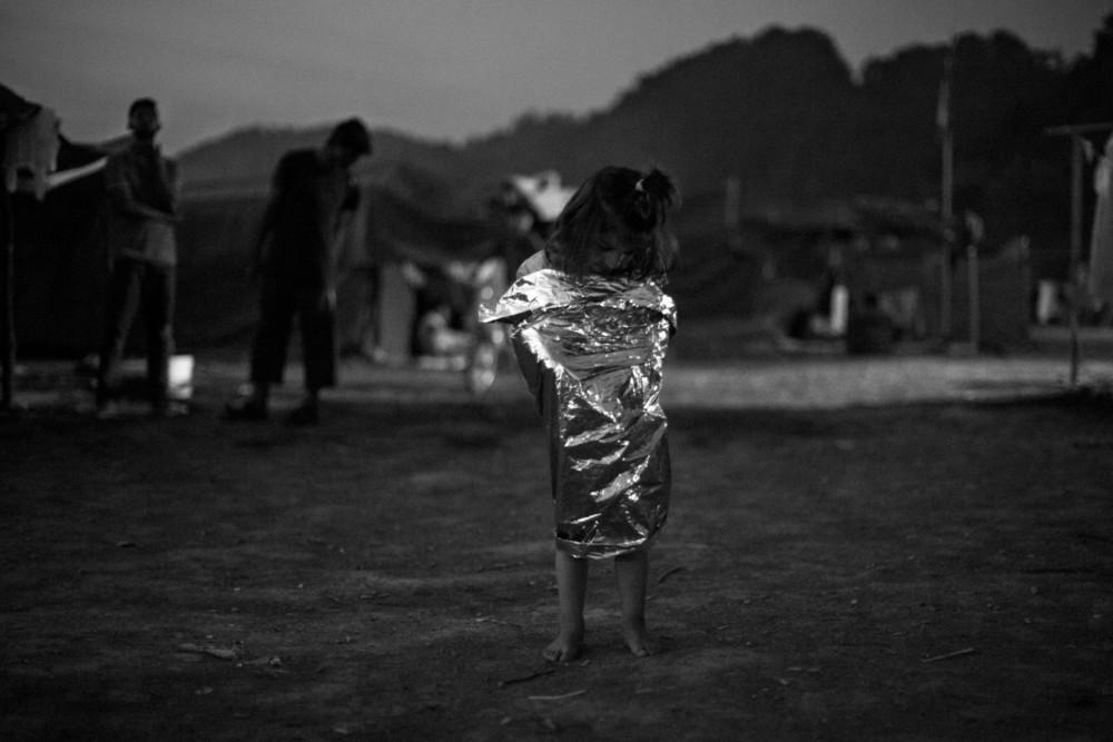 Fot. Maciej Łuczniewski, Agencja Fotograficzna Reporter Bośnia i Hercegowina. Irańskie dziecko stoi owinięte folią rozdawaną przez NRC na głównej ścieżce obozu dla uchodźców w Velikiej Kladuąy. Wśród tamtejszych imigrantów jest duża grupa irańskich chrześcijan, którzy uciekli ze względu na prześladowania. 7 sierpnia 2018