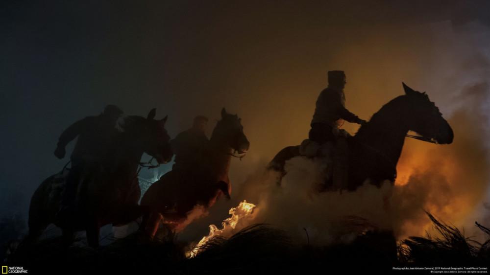"""Fot. José Antonio Zamora, """"HORSES"""" - III miejsce w kategorii """"Ludzie"""". Każdego roku w święto św. Antoniego obchodzi się w Hiszpanii ceremonię oczyszczenia zwierząt, zwaną Las Luminarias. W prowincji Avila konie i jeźdźcy przeskakują ogniska podczas rytuału, który trwa od XVIII wieku."""