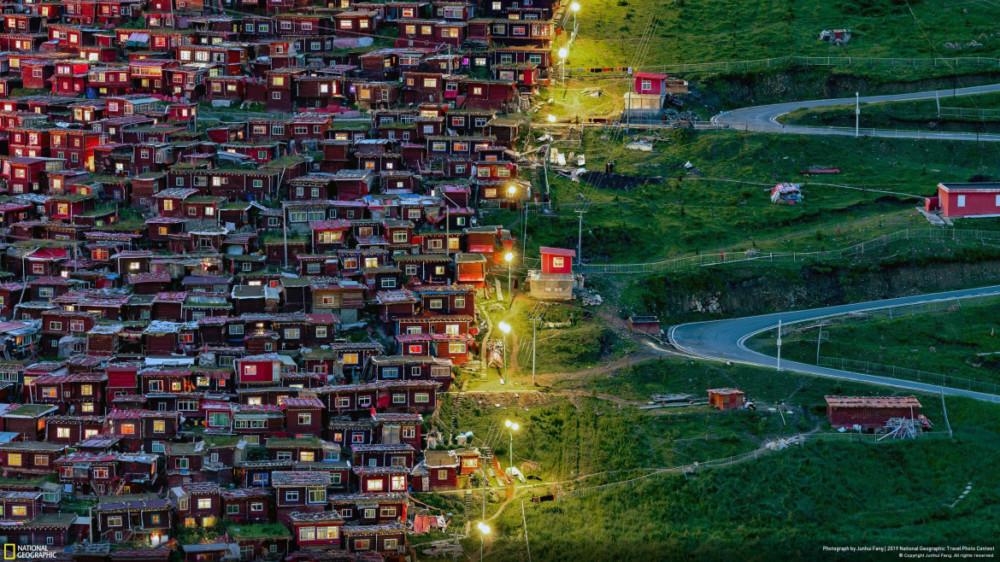"""Fot. Junhui Fang, """"FOLLOW THE LIGHT"""" - nagroda publiczności w kategorii """"Cities"""". Zdjęcie zostało zrobione w Akademii Buddyjskiej Seda Larung Gar. Dojazd do Larung Gar z najbliższego miasta zajmuje około 14 godzin, a podróż jest dość trudna z powodu górskich dróg. Widok pokazuje małe czerwone domy po lewej stronie i puste zielone drogi po drugiej stronie. Mnisi podążają za światłami, aby wrócić do domu."""