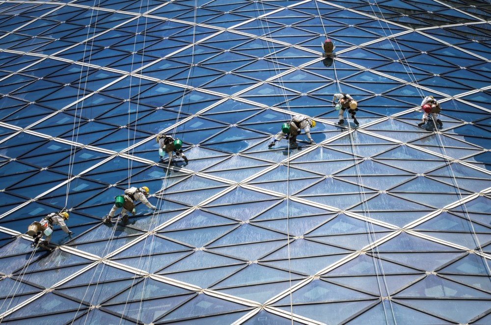 """""""Zdjęcie jest przykładem potrzebnej interakcji pomiędzy ludźmi i budynkami. Bez zapracowanych ludzi czyszczących gigantyczne szklane ramy wieży, budynek wyglądałby brzydko."""" Fot. Volker Sander"""